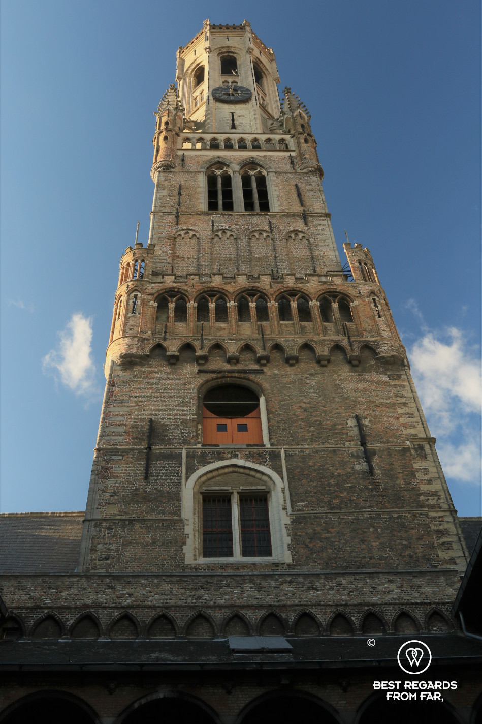 The Belfry of Bruges, Belgium, against a blue sky.