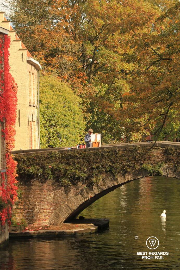 A painter painting Bruges' skyline on a bridge
