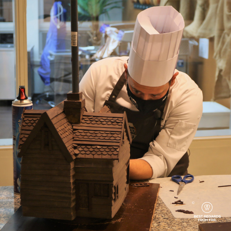 A chocolatier handcrafting a house made of chocolate