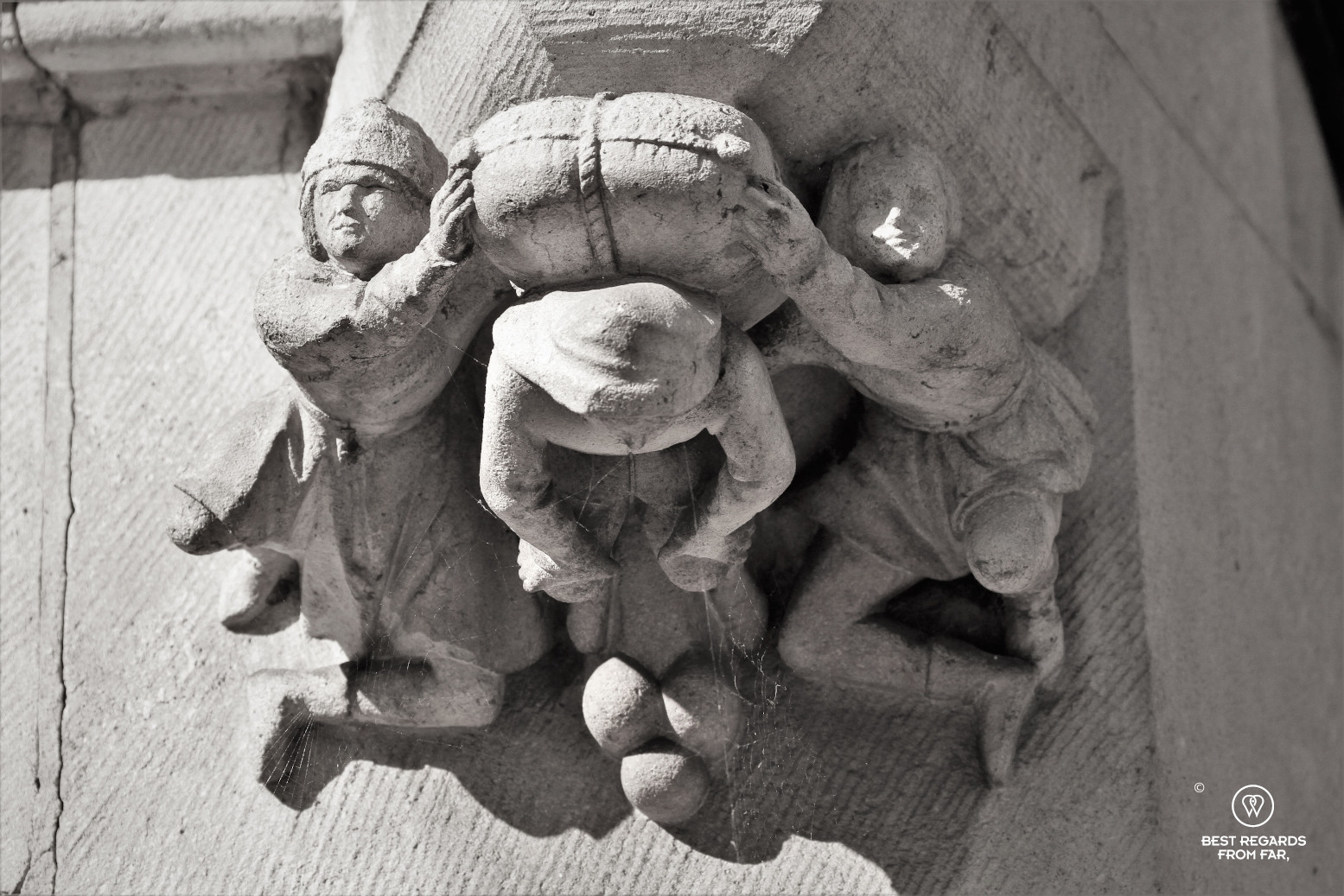 Detail on a building showing how cargo was carried during medieval times in Bruges