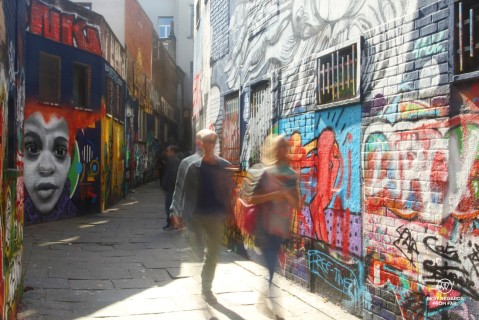 Two people walking through the colourful graffiti street in Ghen, Belgium