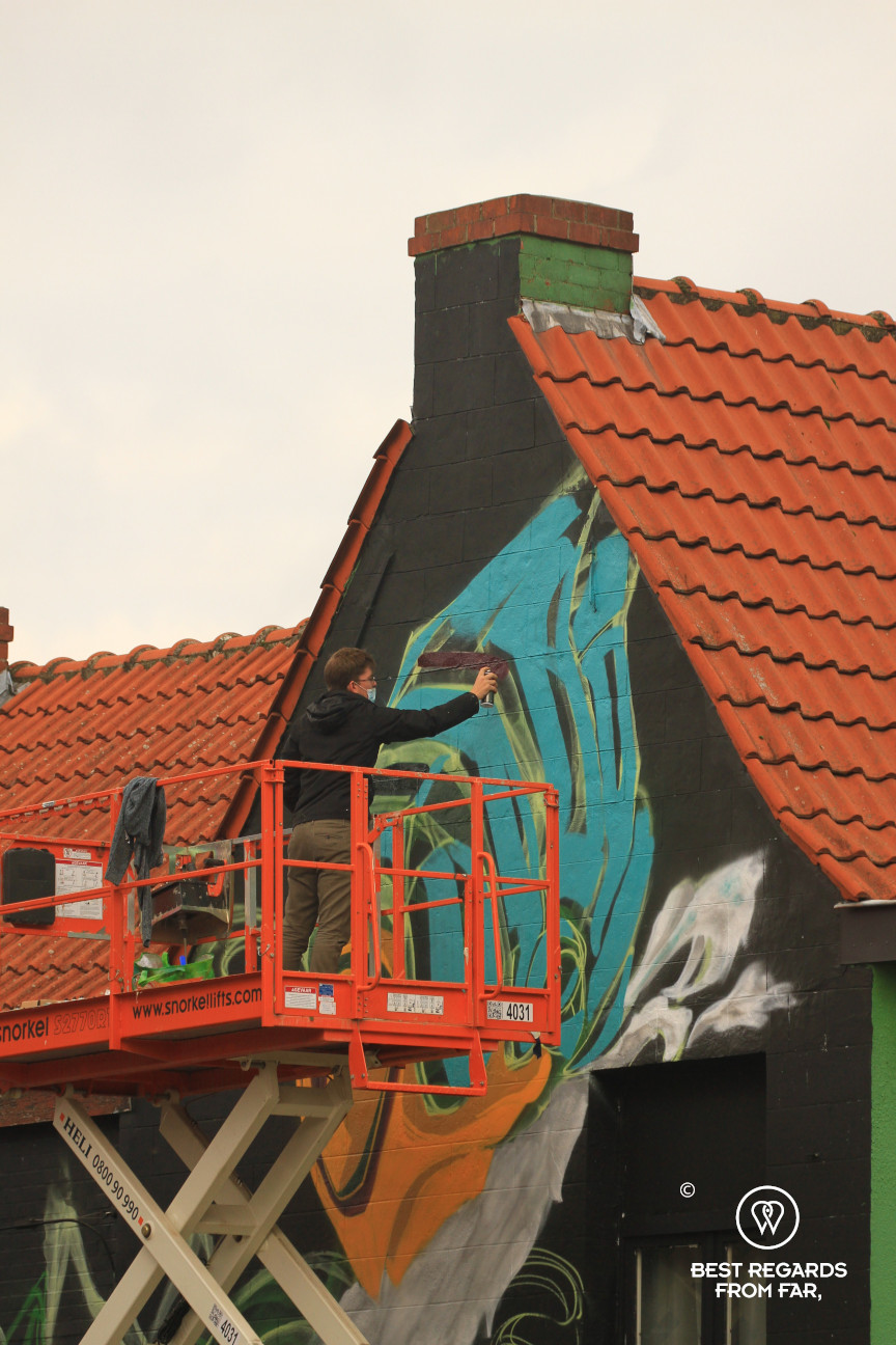 Street artist at work with graffiti on a facade in Ghent, Belgium