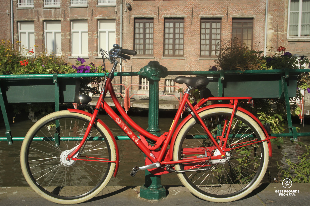 Red bike in front of a canal in Ghent