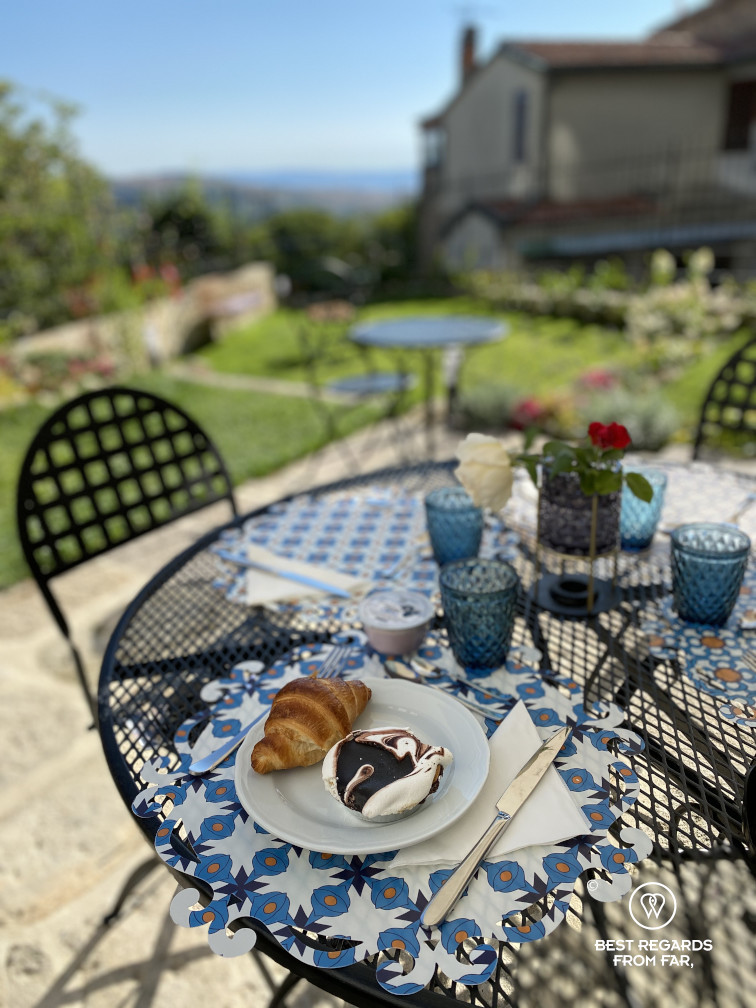 Croissant and Tuscan specialty on a set table for breakfast in the garden with a view