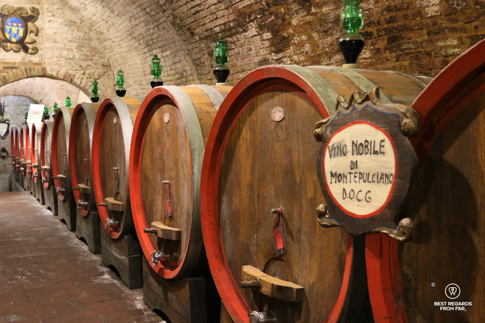 Oak wine barrels in a brick vaulted wine cellar in Italy