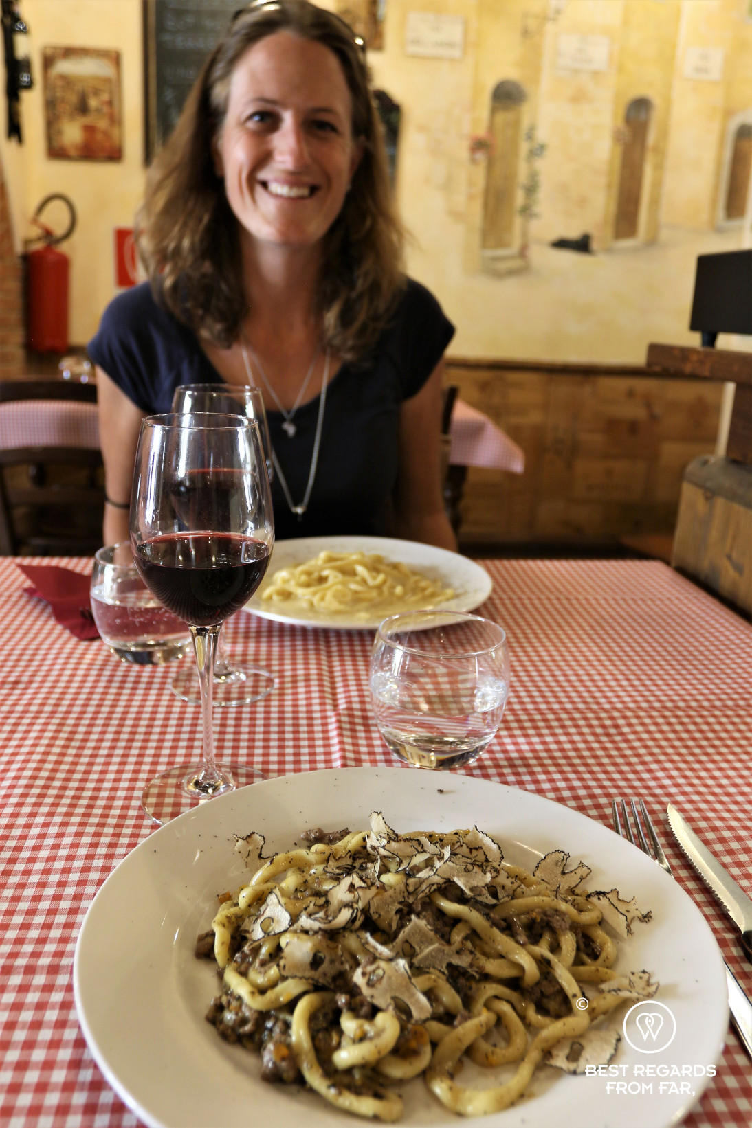 Woman smiling in an Italian restaurant with a table set with local speacialties