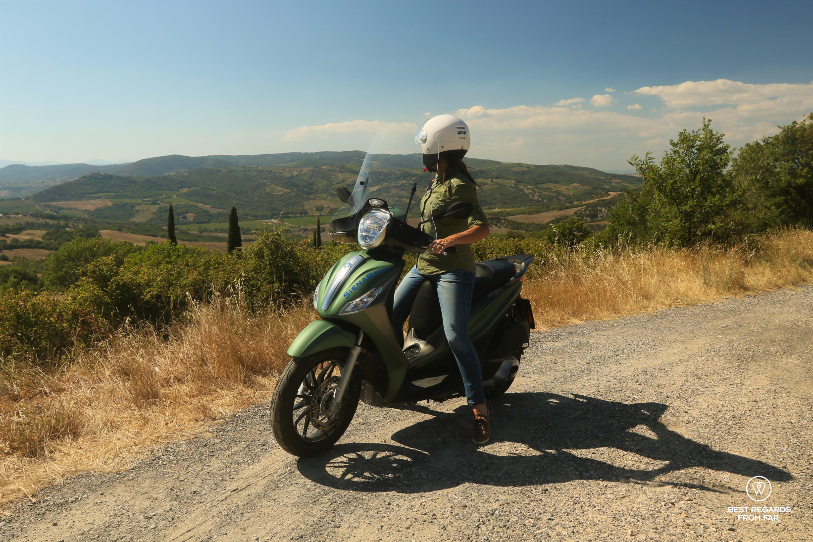 Woman on a green Vespa enjoying the view on rolling hills in Tuscany, Italy
