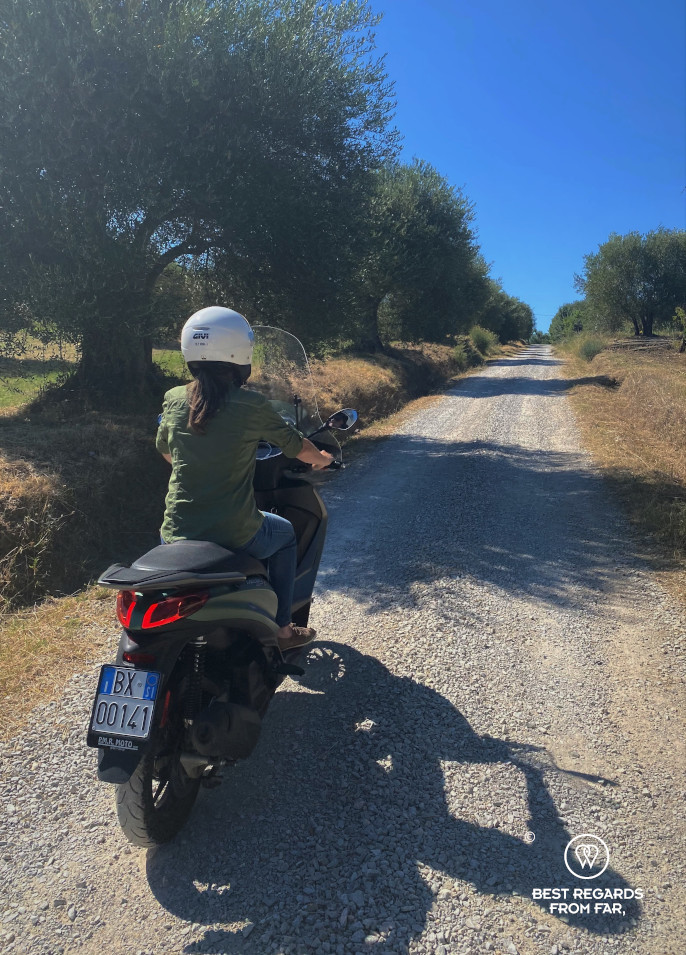 Woman driving a Vespa on a dirt road through an olive grove