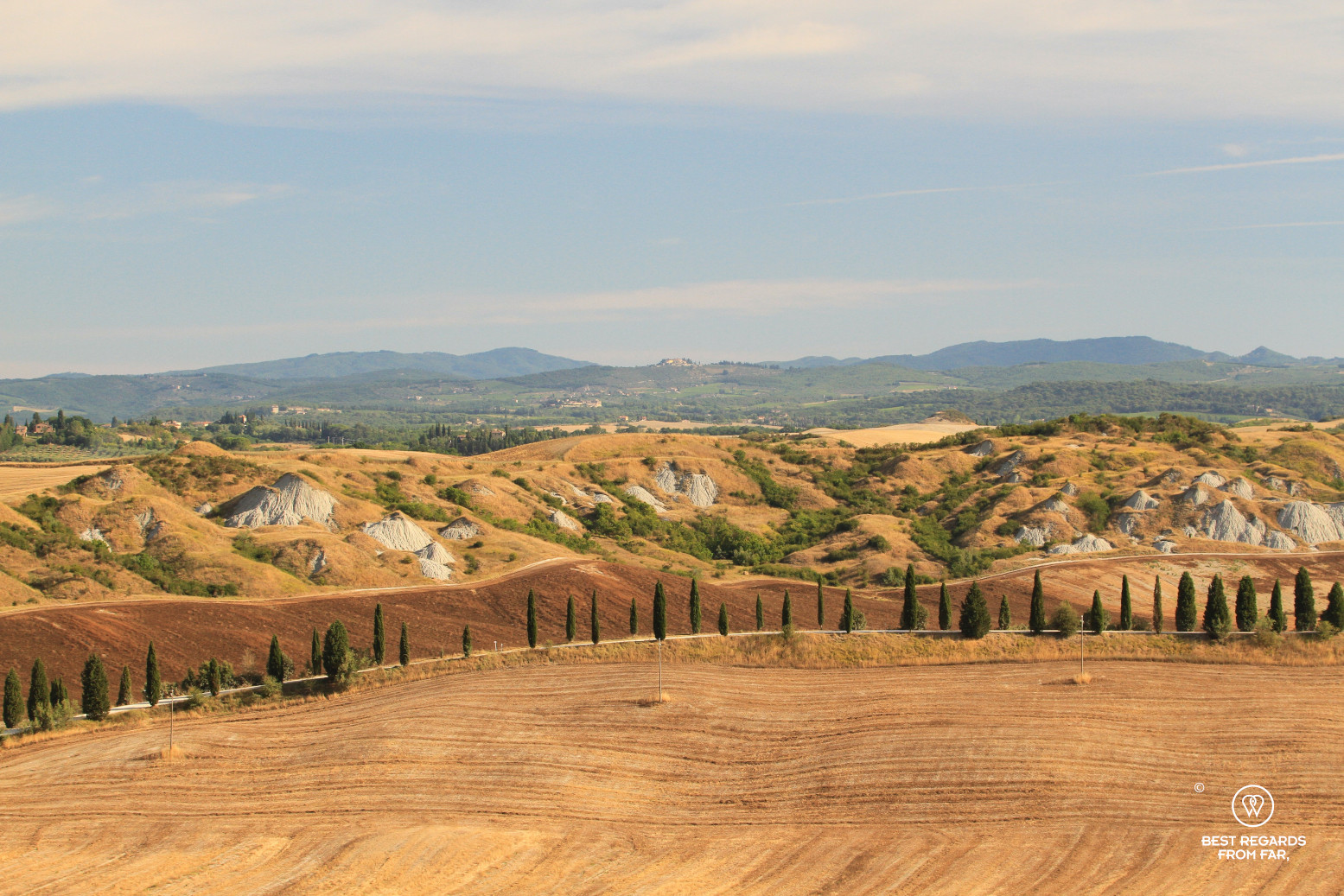 Typical Tuscan landscape with wheat fields and cypress trees, Italy
