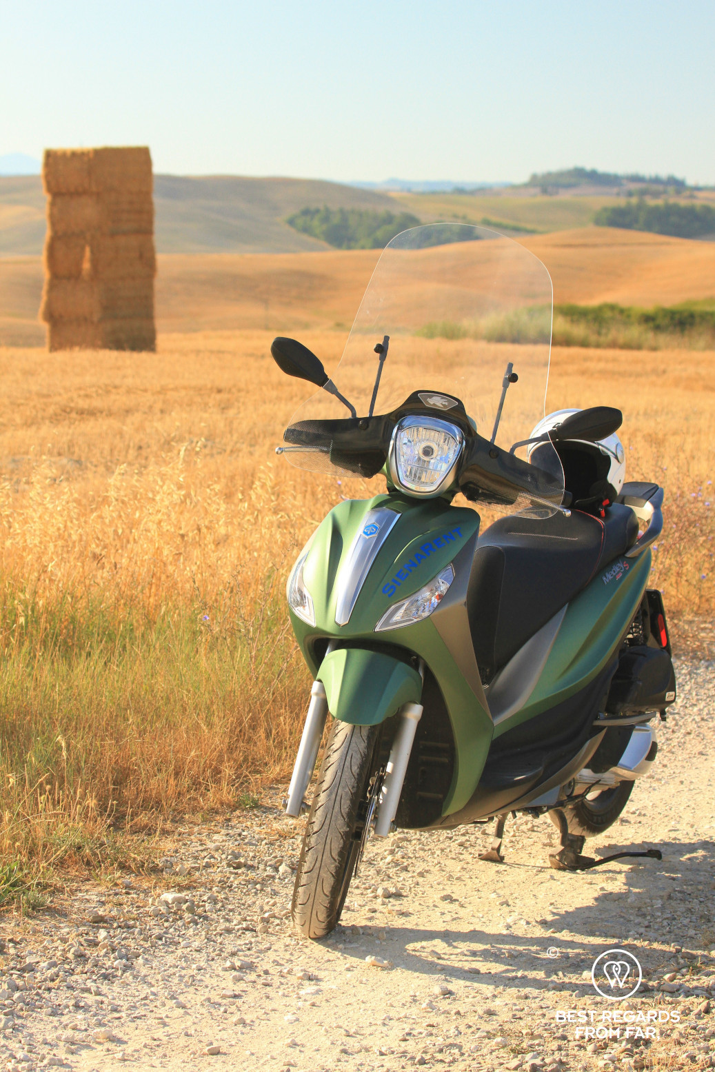 Green Vespa parked in a barley field in Tuscany, Italy