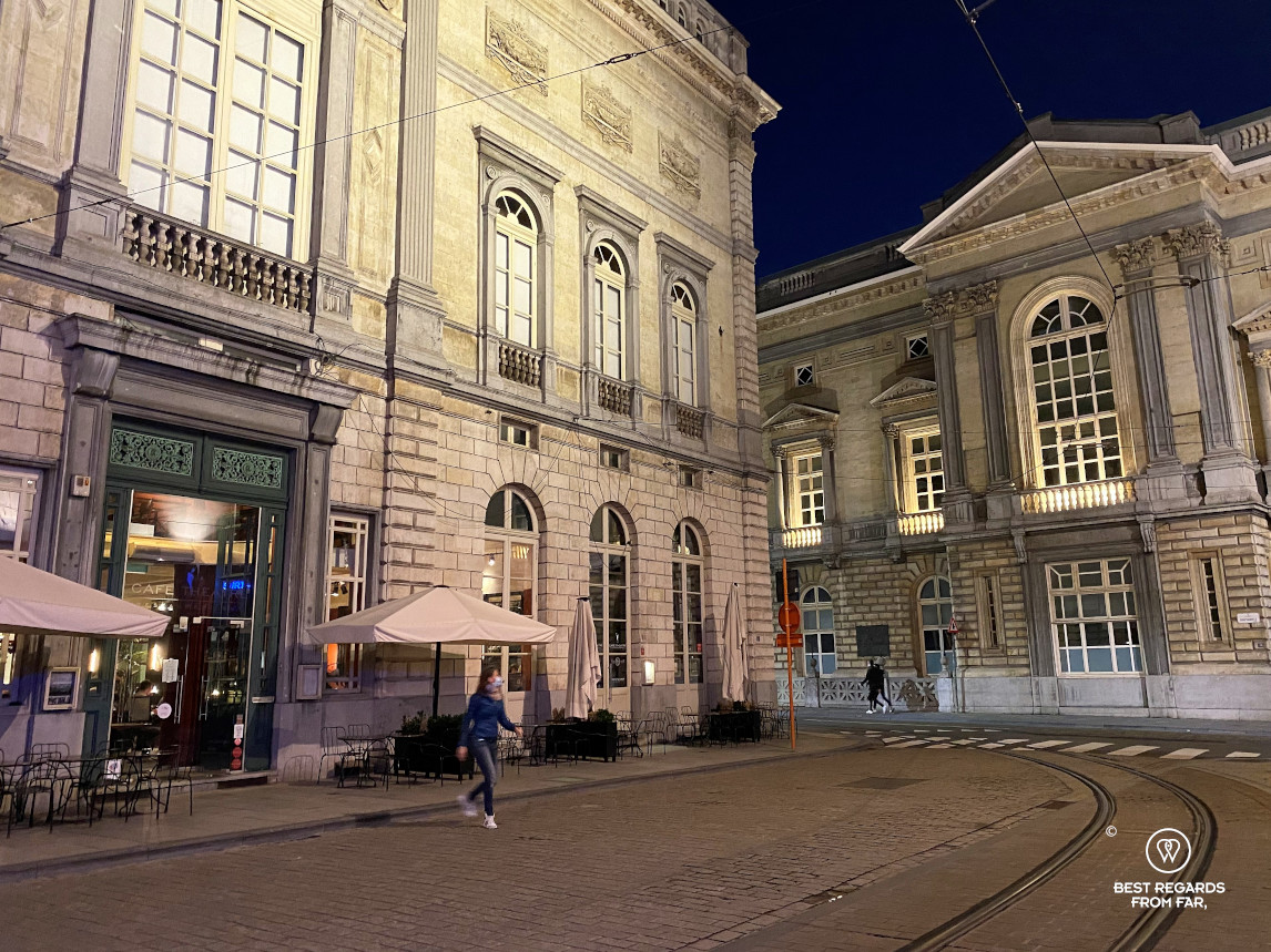 Woman crossing an empty street in front of the Opera House and Café Théâtre, Ghent, Belgium