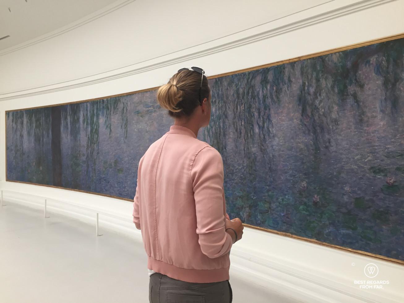 Woman admiring The water lilies by Claude Monet at Musée de l'Orangerie, Paris