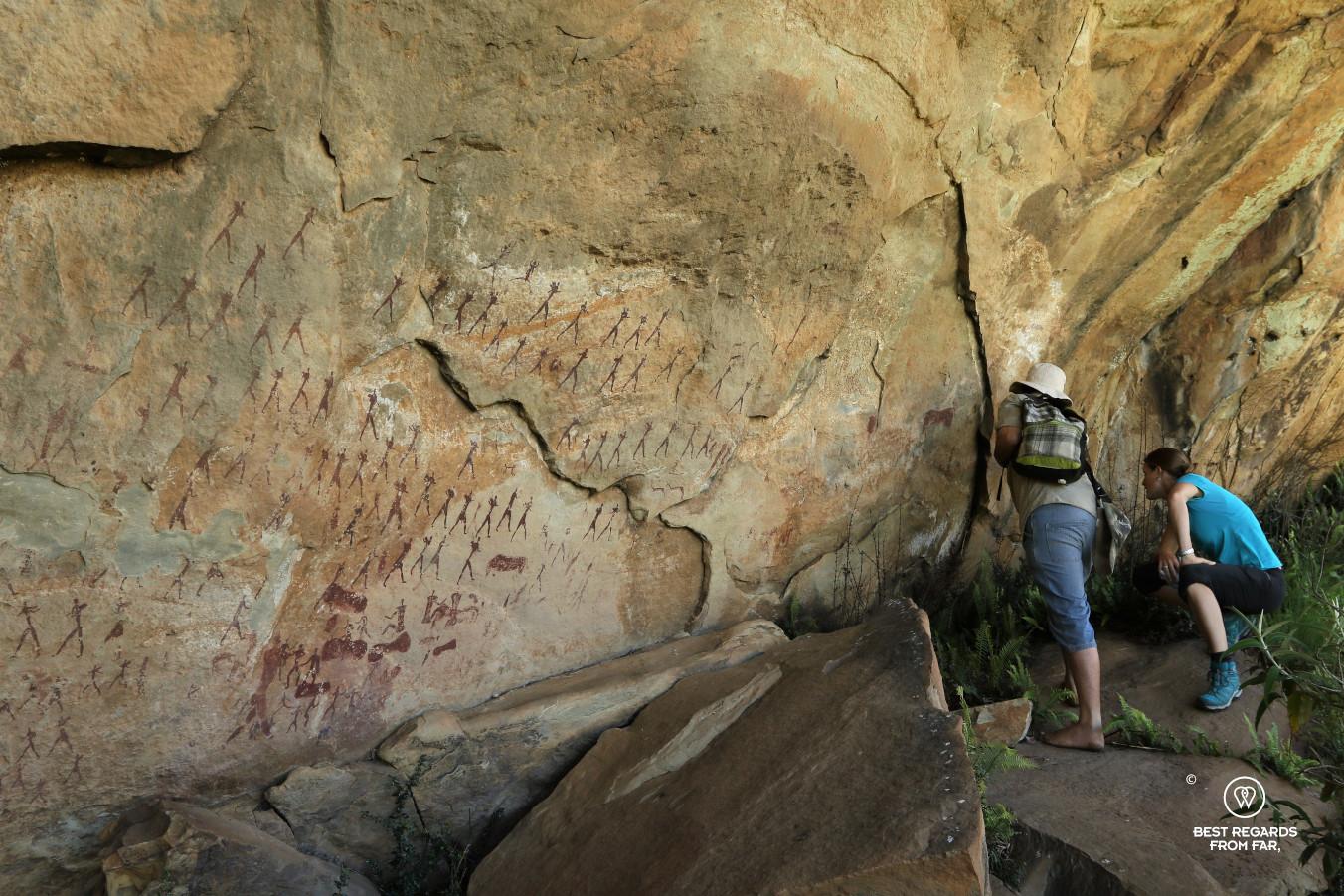 Hikers studying Bushmen rock art in the Drakensberg, South Africa.