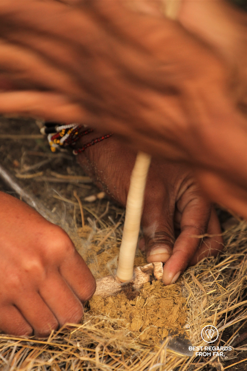 San men making a fire by quickly rotating a dry stick on dry residues, Botswana.