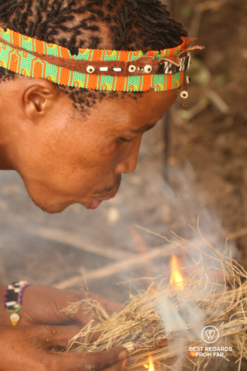 San man blowing on a fire, Botswana.