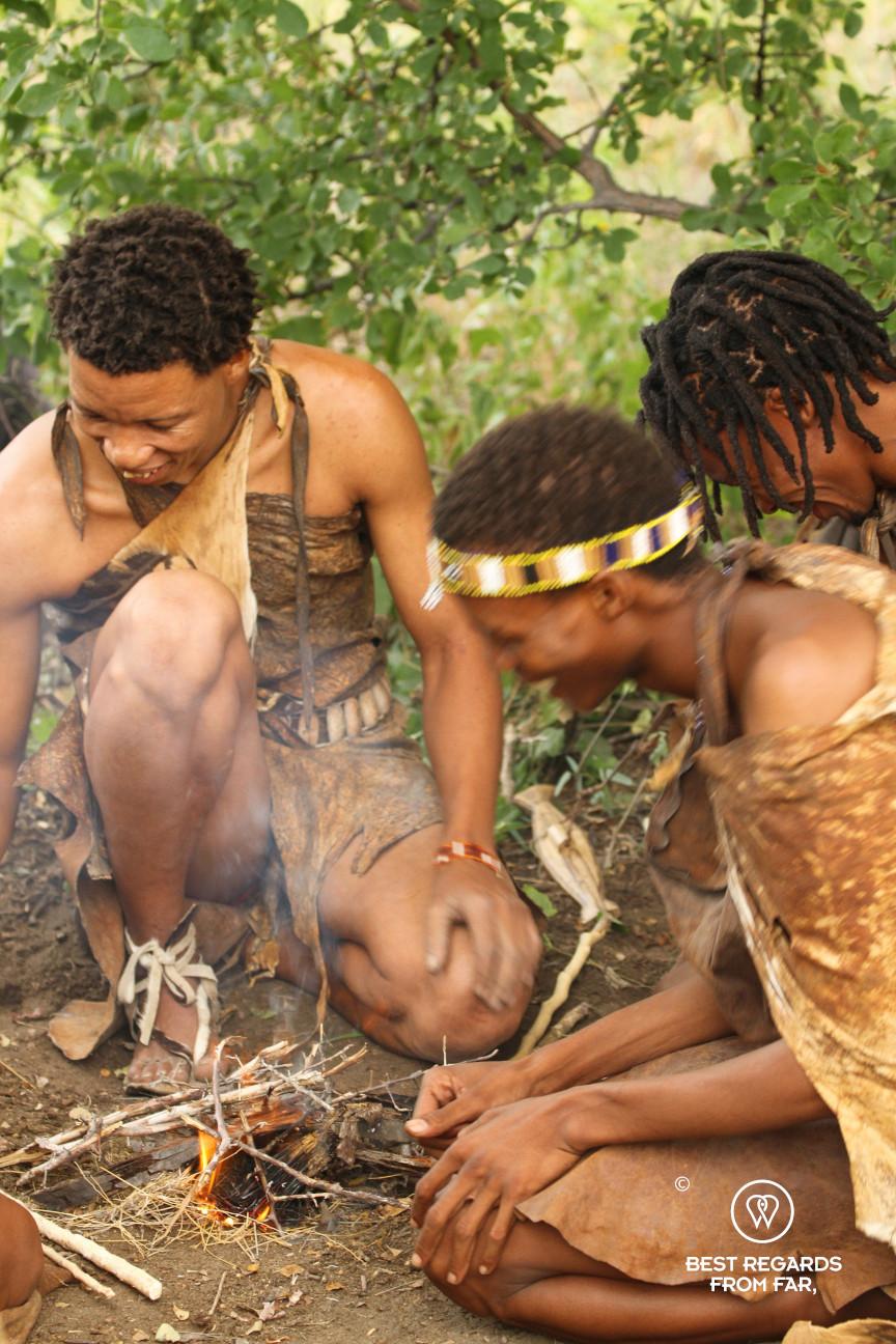 San men laughing around a fire, Botswana.