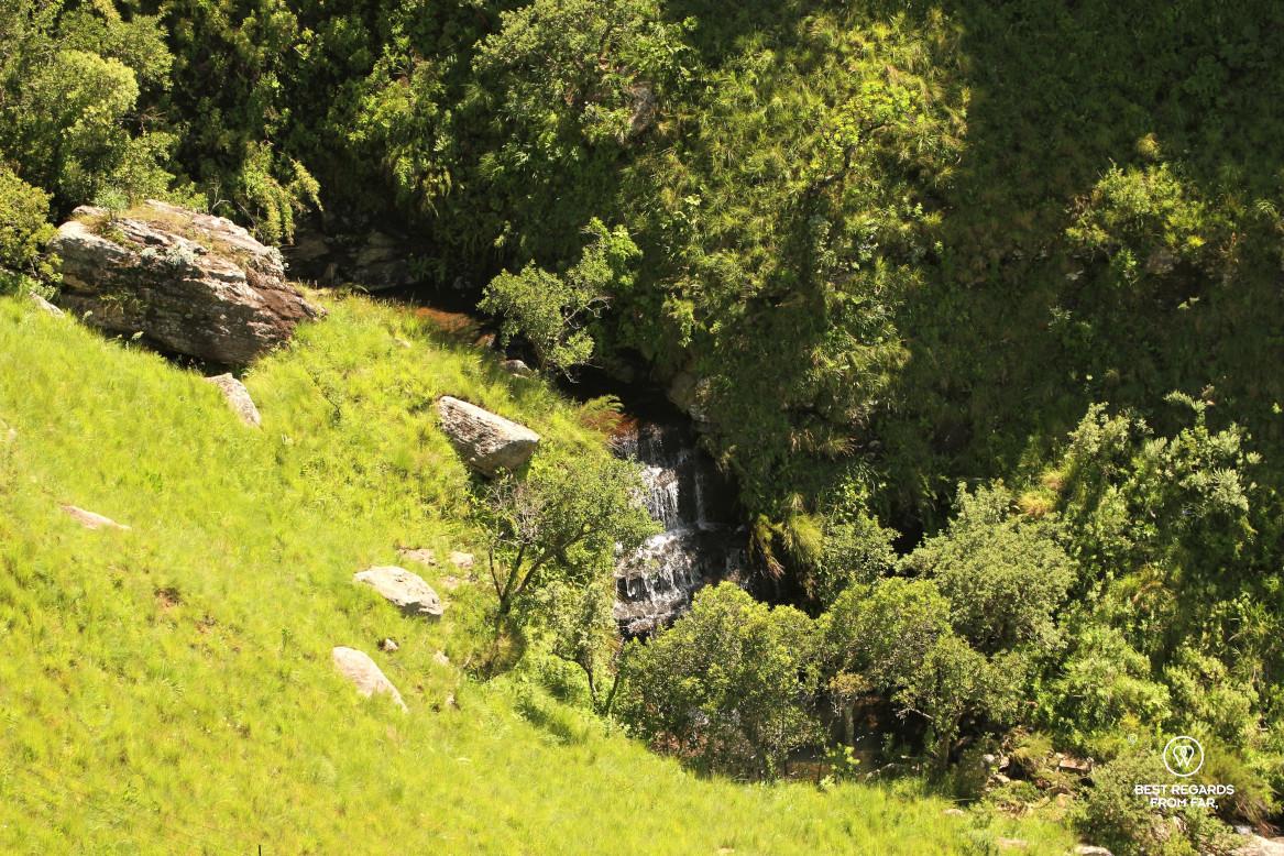 Waterfall amongst green mountain slopes, Drakensberg, South Africa