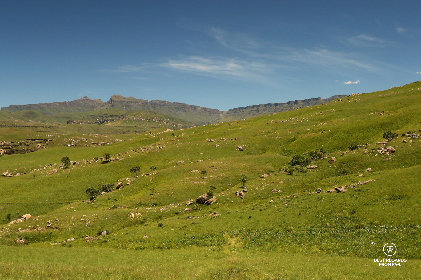 Sani Pass in the in the background with the green rolling hills of the Drakensberg.