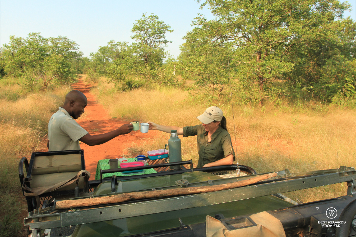 Author Claire Lessiau cheering with EcoTracker instructor Norman Chauke by the Land Rover