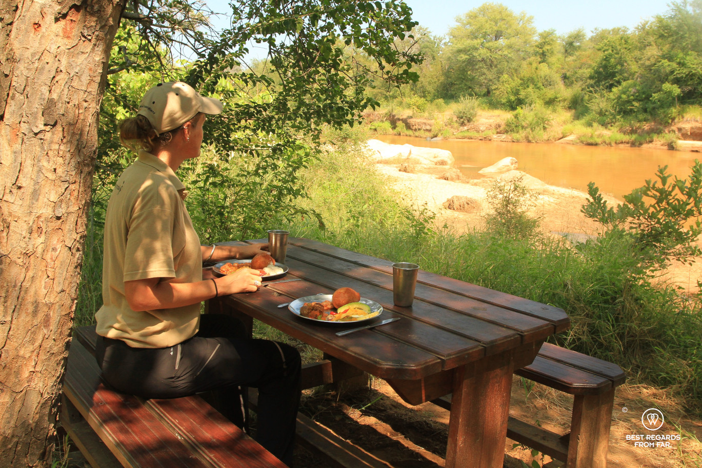 Person having lunch on a picnic table in bush camp overlooking the Selati River, South Africa
