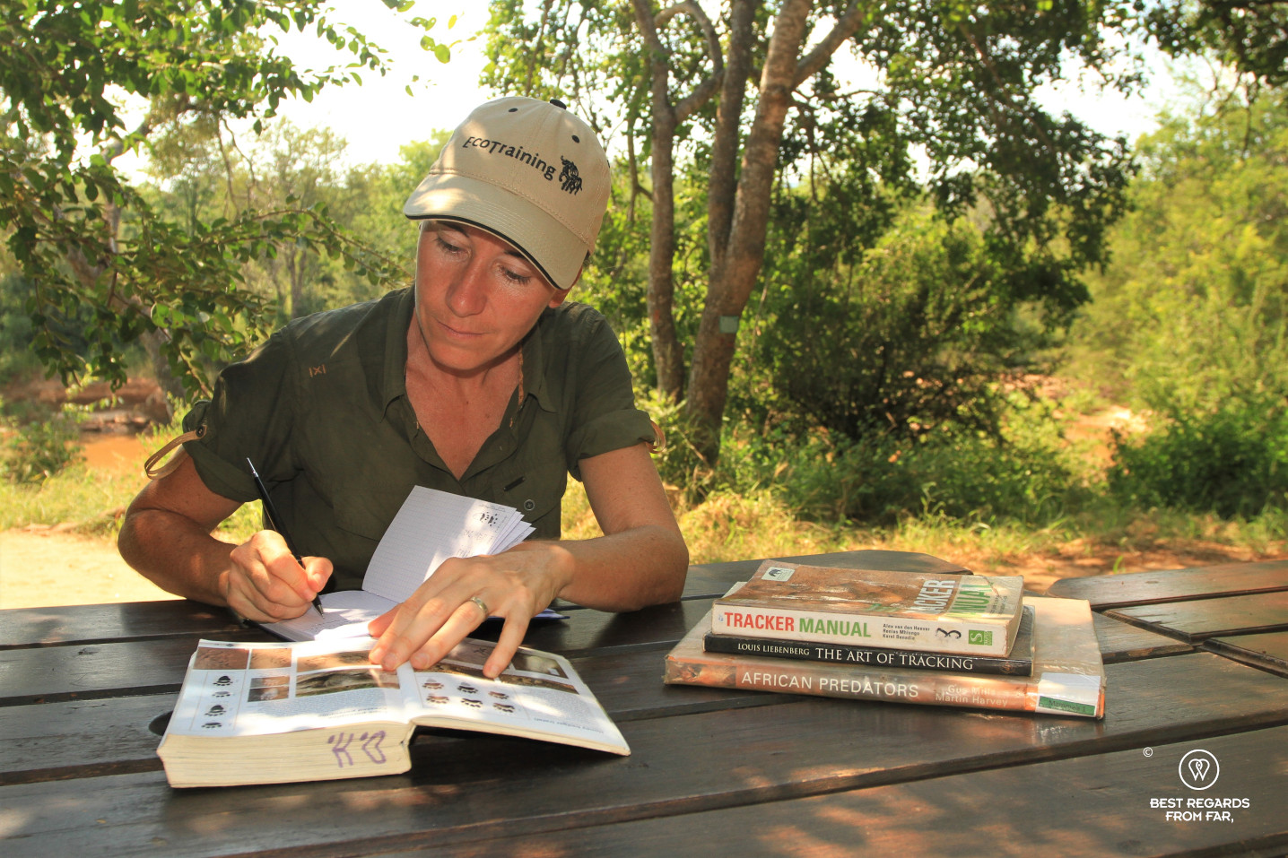Author Claire Lessiau studying the theory of tracking in a book at the Selati camp