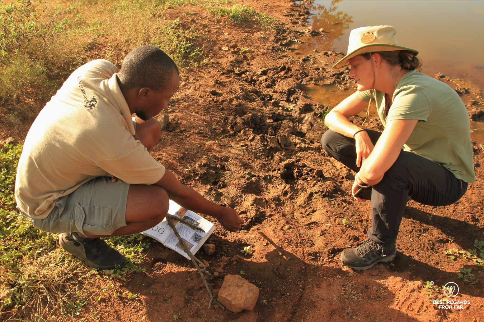 EcoTracker instructor Norman Chauke analizing a zebra track in the red mud with a student