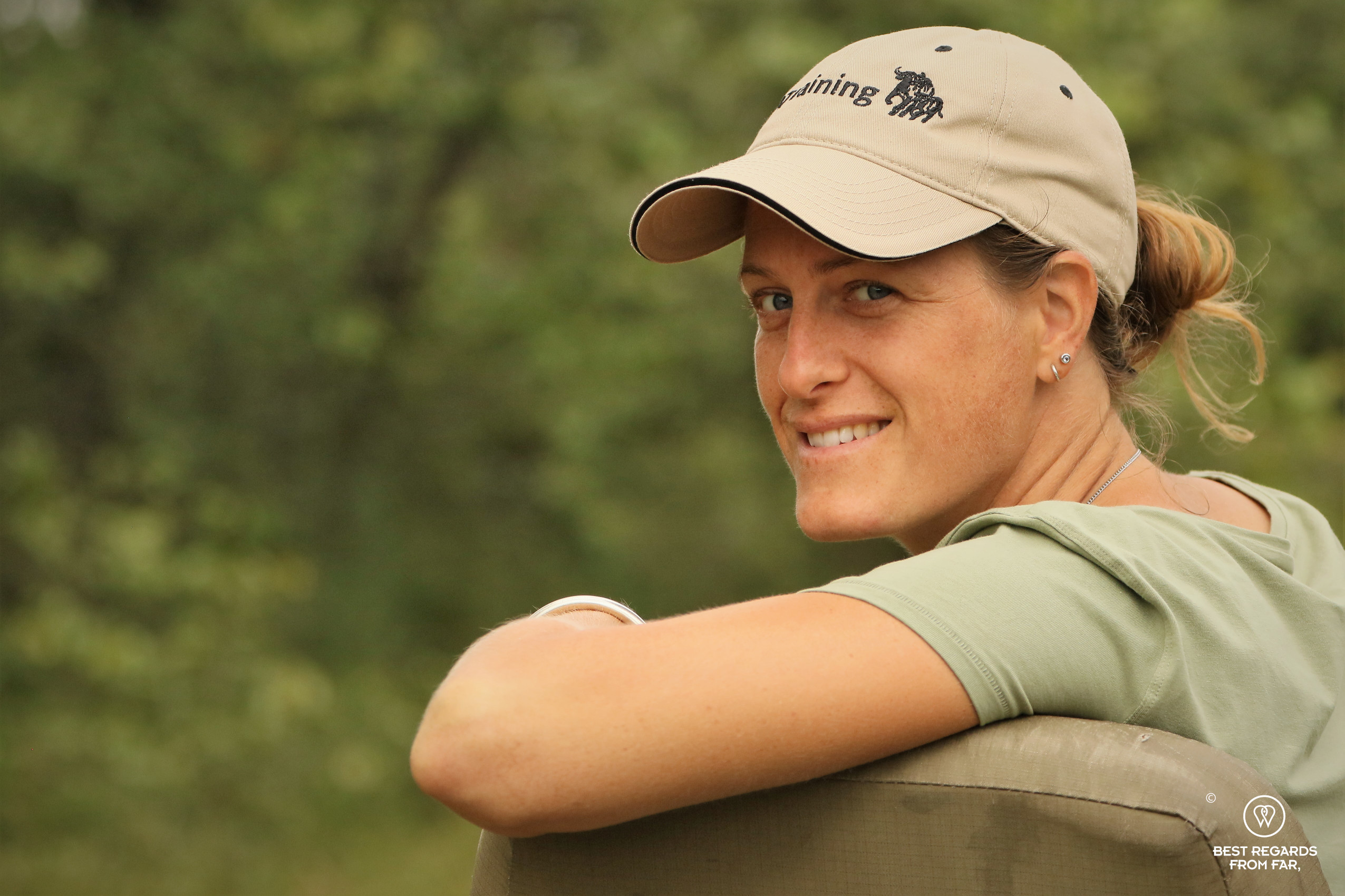 Photographer Marcella van Alphen with an EcoTraining cap looking at the viewer from the tracker seat