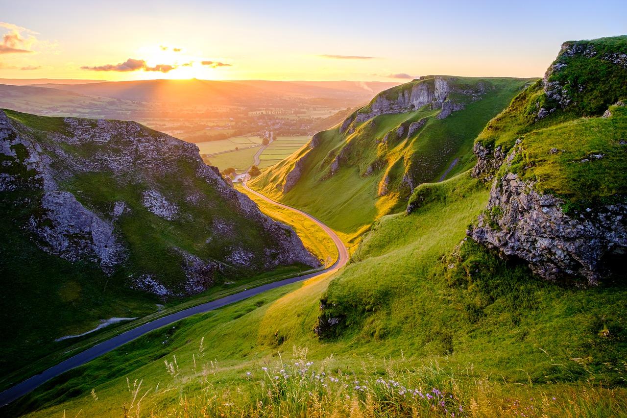 Road winding through Peak District, UK, at sunset.