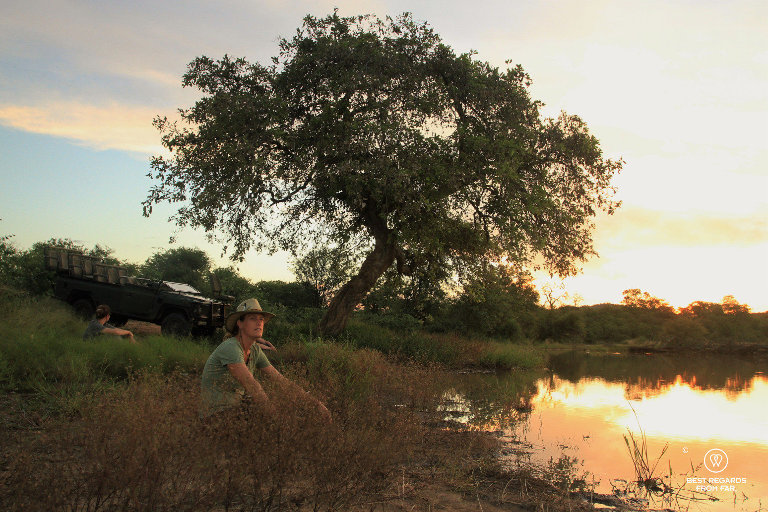 Safari-goer seated by a pond for sunset in the African bush