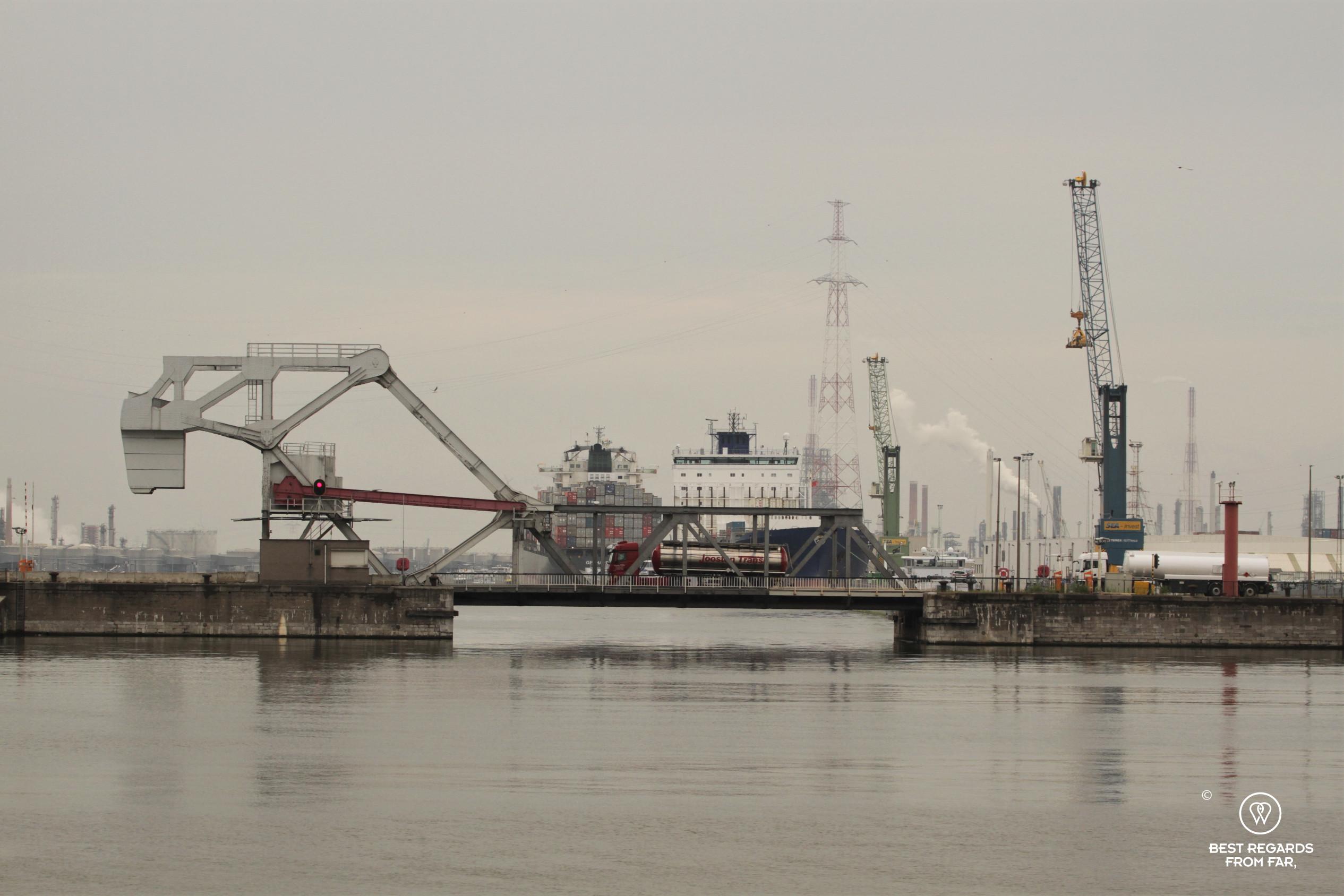 Cranes, chimneys, bridge and cargoships in the industrial harbour of Antwerp, Belgium
