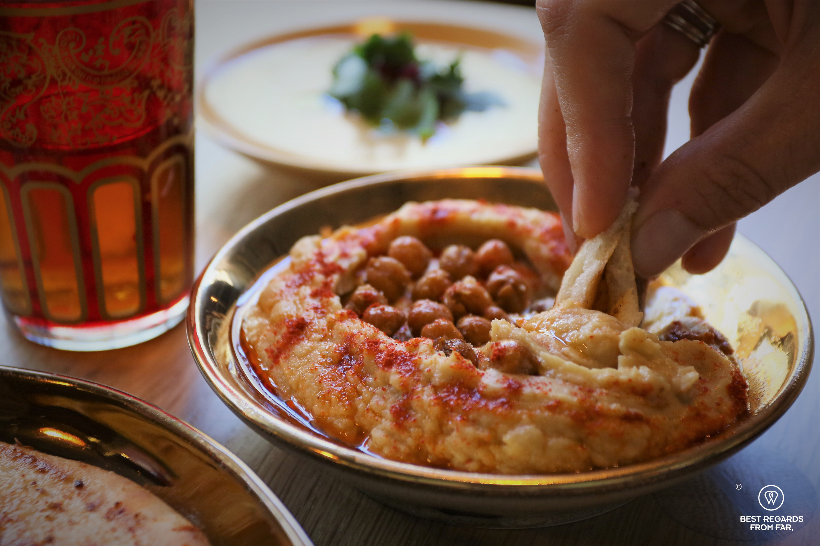 Close up on a guest taking some hummus with flatbread at the Chefs Warehouse Mazza, Cape Town