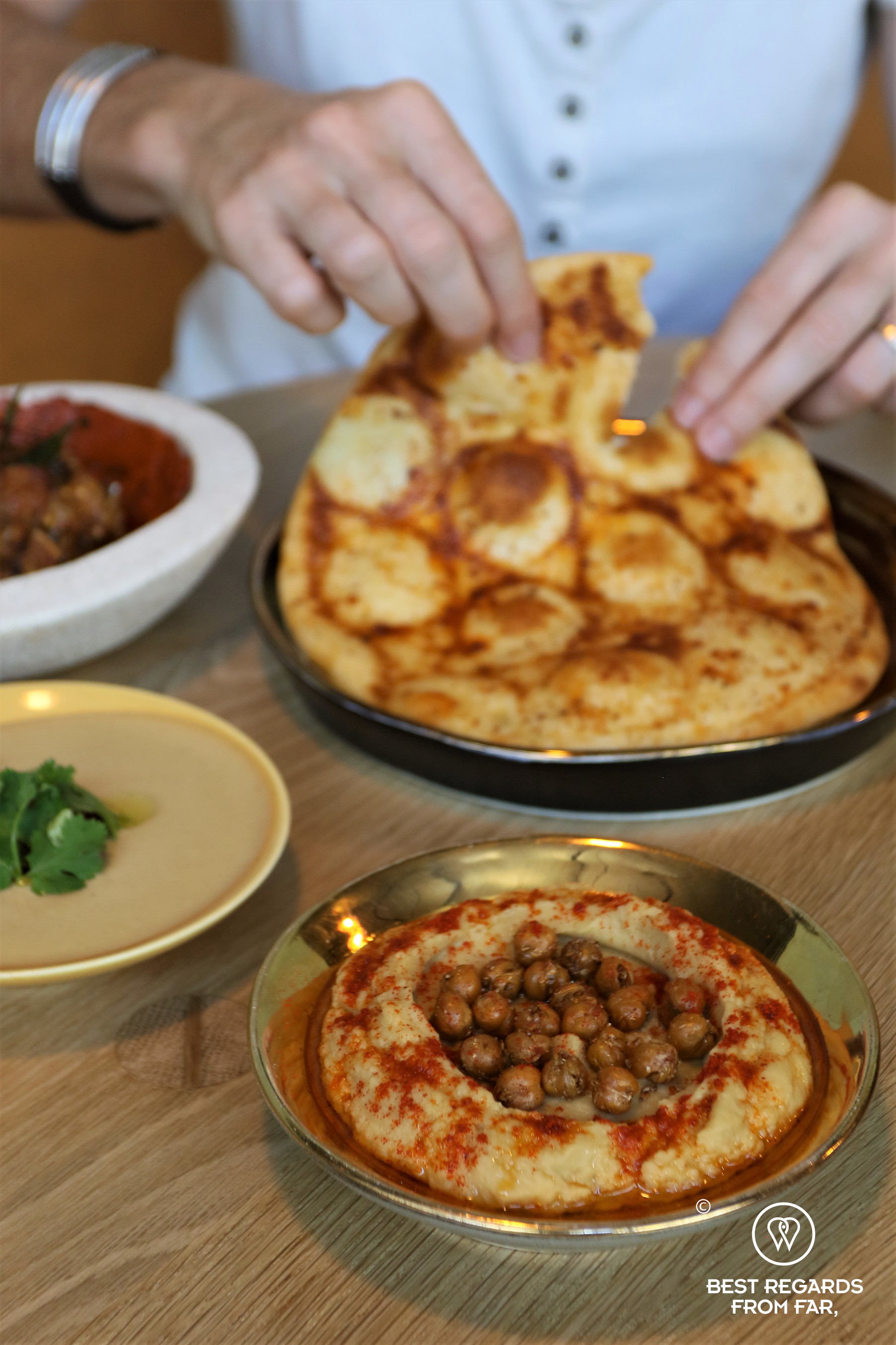 Guest taking some taboon flatbread with hummus, labneh & nduja sausage mezze, Mazza, Cape Town