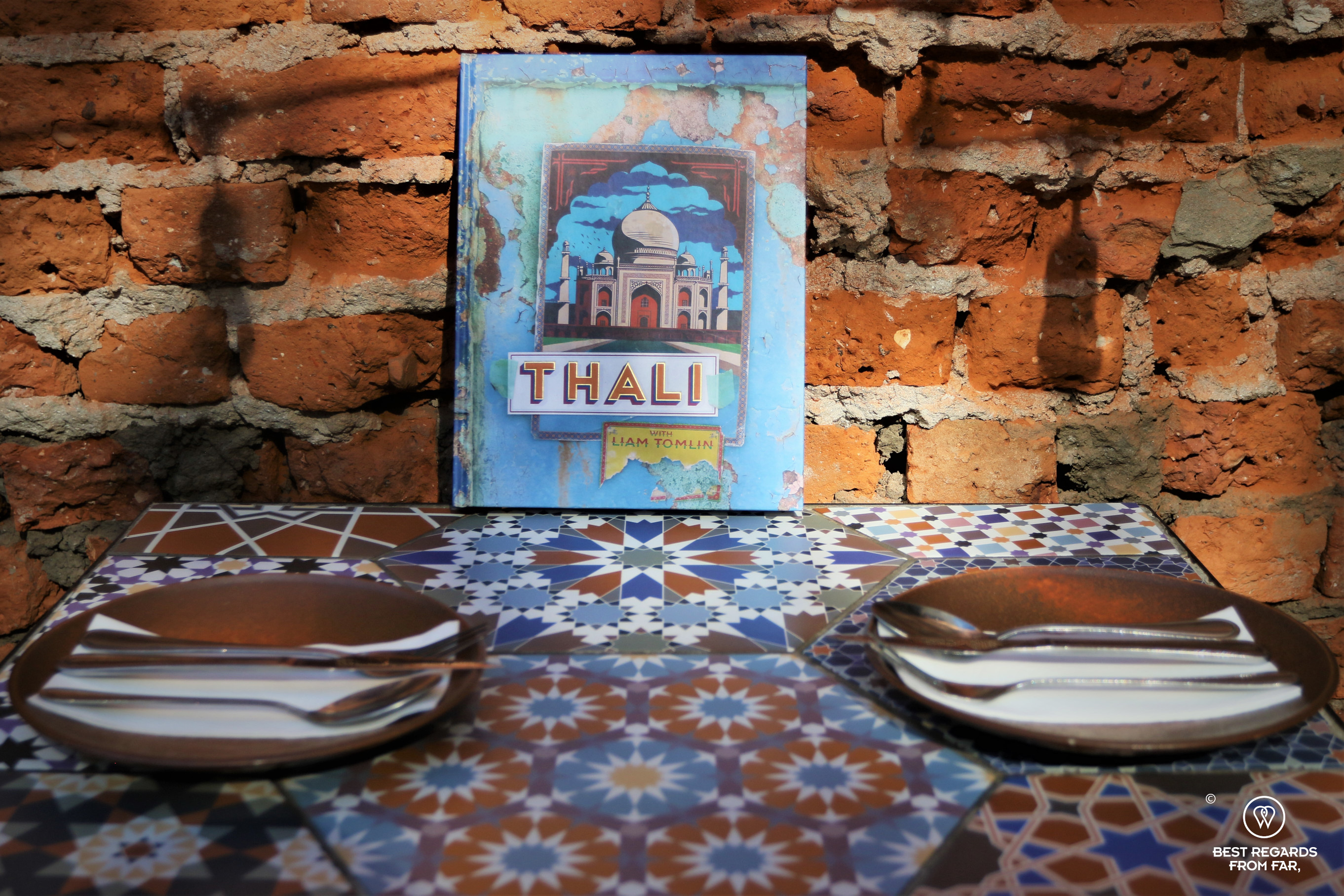 Table by a brick wall with the Thali cooking book in the courtyard of Thali, Cape Town