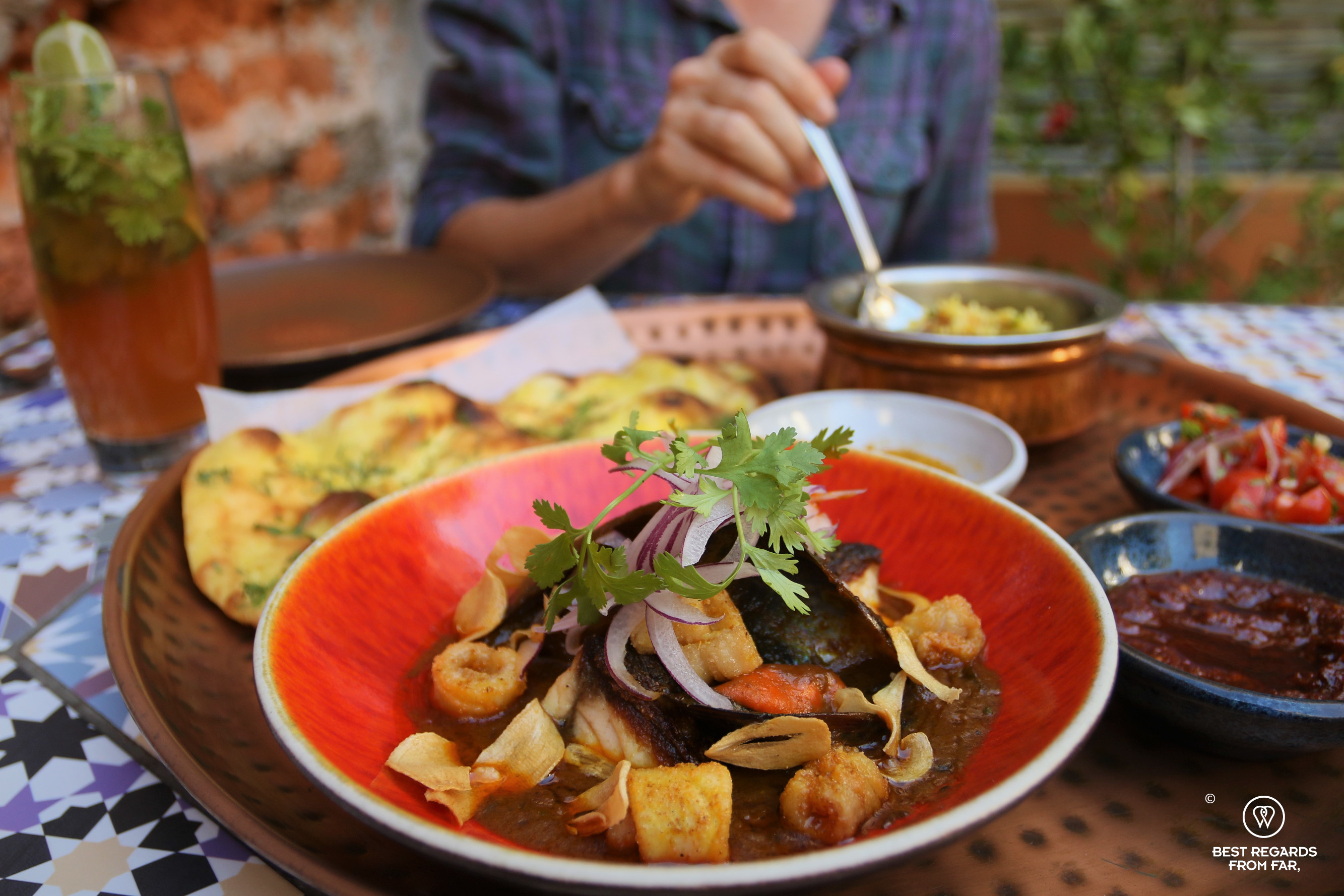Seafood curry on the foreground with a guest in the background at Thali, Cape Town