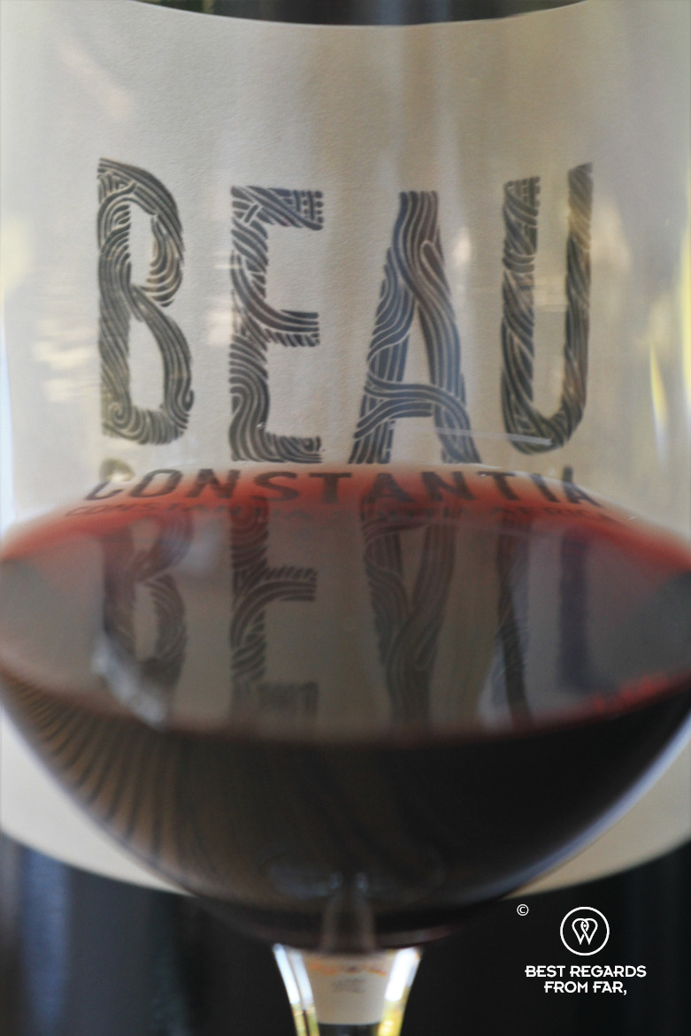 Red wine in a glass with Beau Constantia bottle, Constantia wine route, Cape Town