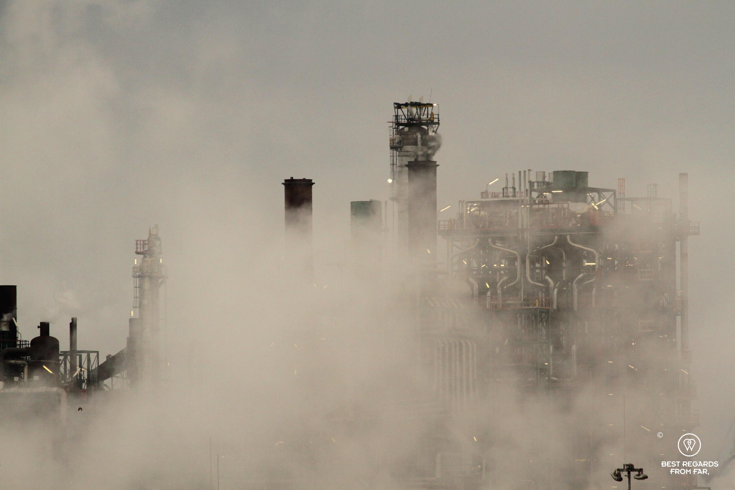 Lit refinery amidst exhaust smoke in the harbour of Antwerp, Belgium