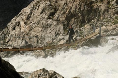 Writer Marcella van Alphen crossing a suspension bridge above powerful white waters