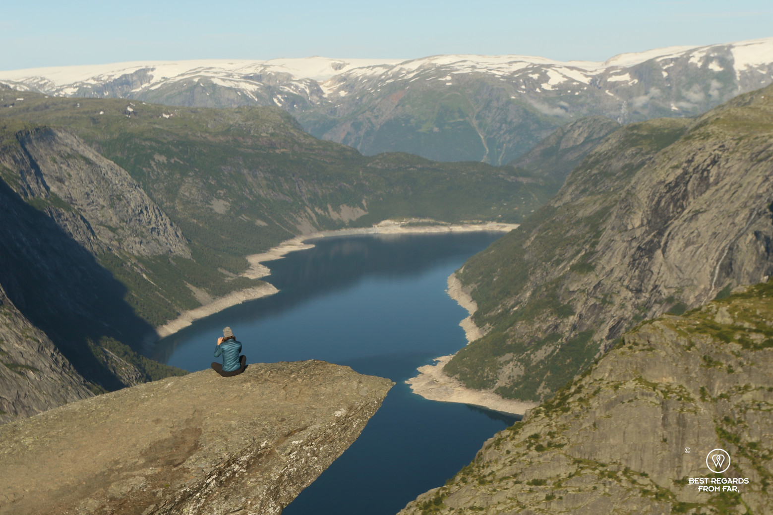 Writer Marcella van Alphen seated on the Trolltunga in Norway overlooking the mountains