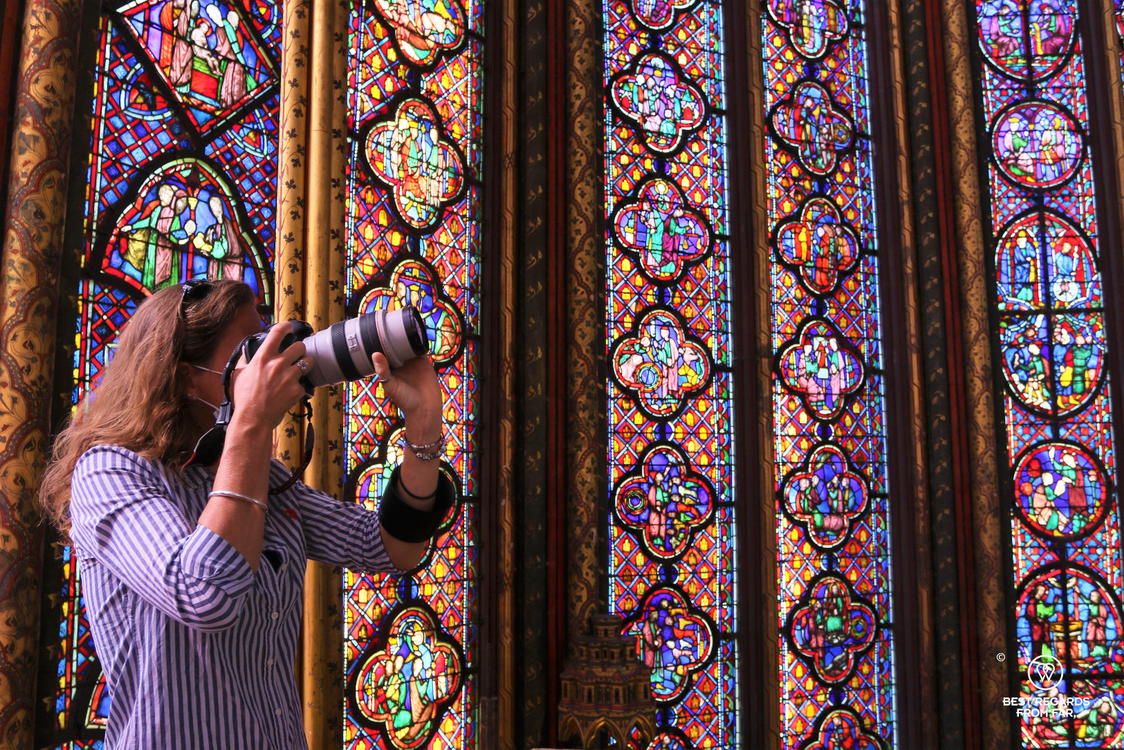 Woman taking a photo of stained-glass windows at La Sainte Chapelle in Paris, France
