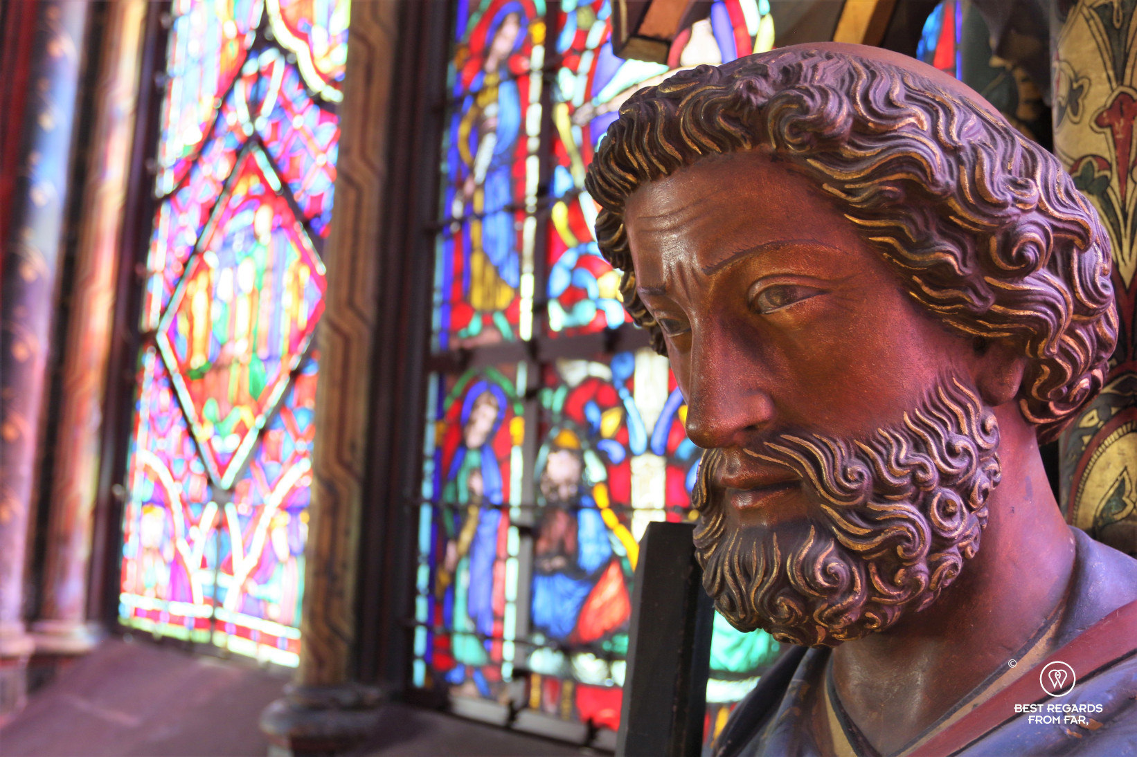 Close-up of a polychromatic wooden sculpture with the colourful stained-glass windows in the background, Paris, France