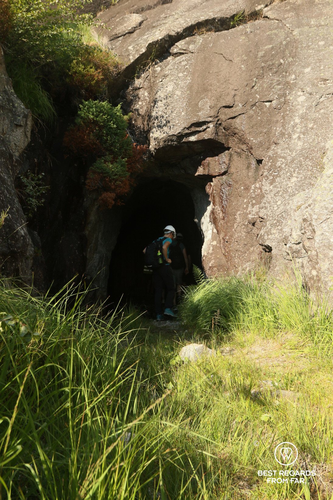 Woman wearing a helmet entering a cave in the mountains