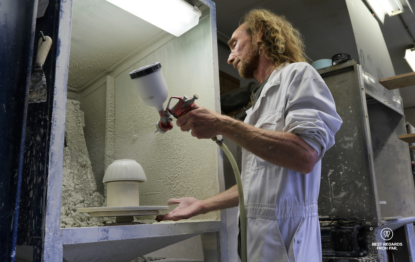 Worker glazing a bowl at the Royal Delft factory, the Netherlands