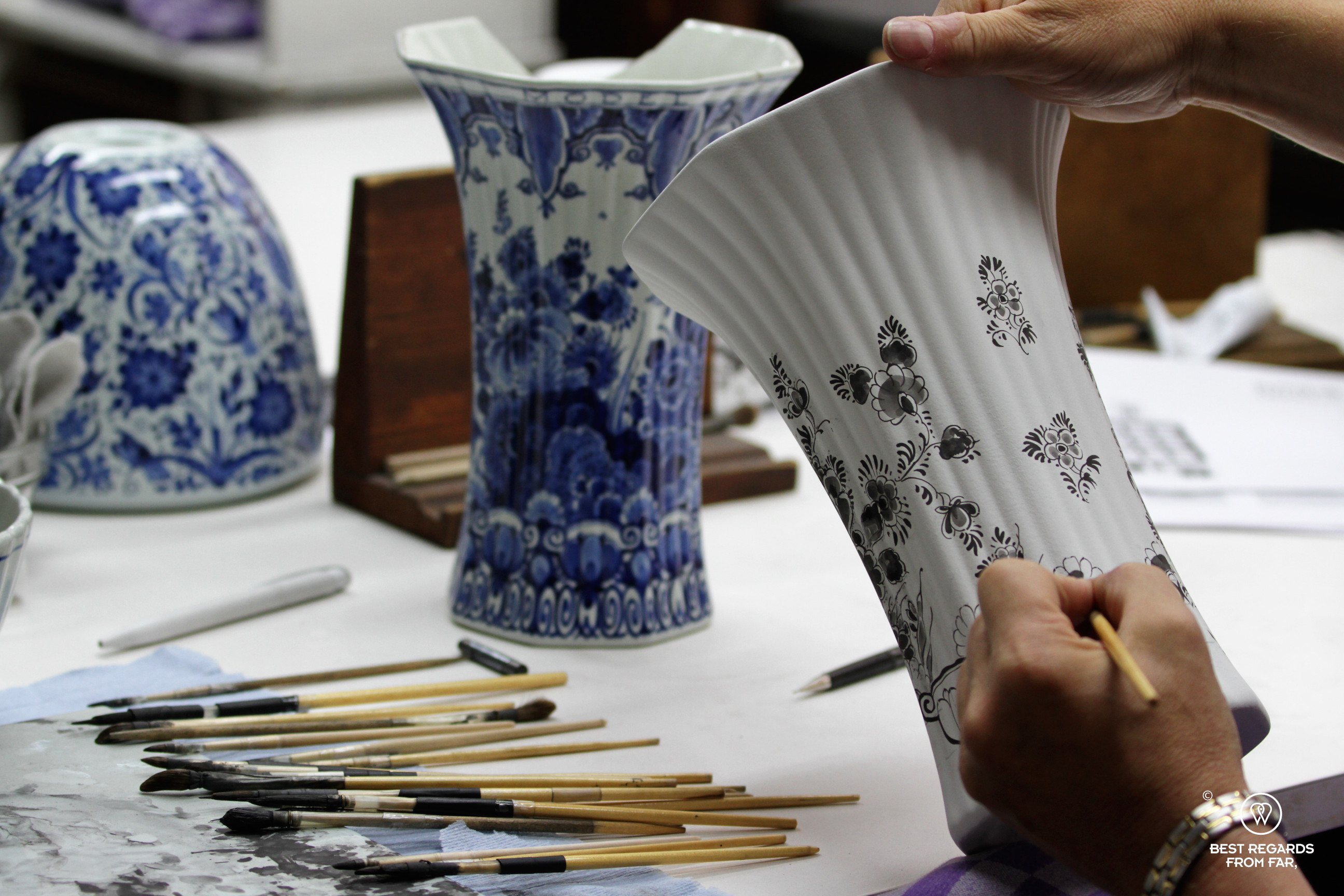 Master painter hand-painitng a vase, the Royal Delft museum, the Netherlands