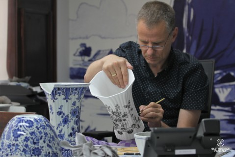 Master painter hand-painting a vase, the Royal Delft museum, the Netherlands