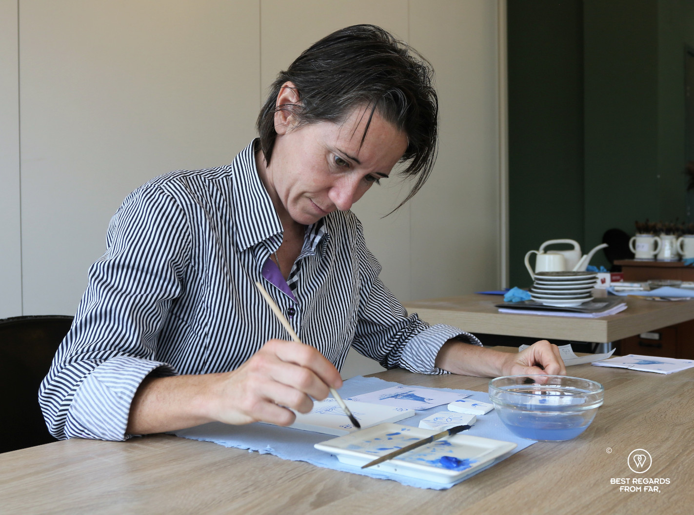Author Claire Lessiau focusing to paint during a tile painting workshop at Royal Delft, the Netherlands