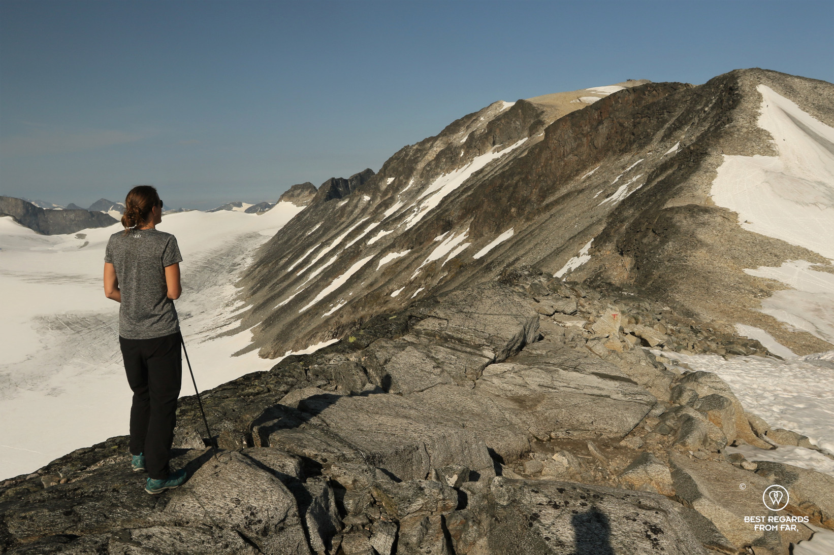 Woman in t-shirt on the rocky trail ascending Norway's highest mountain in Jotunheimen NP