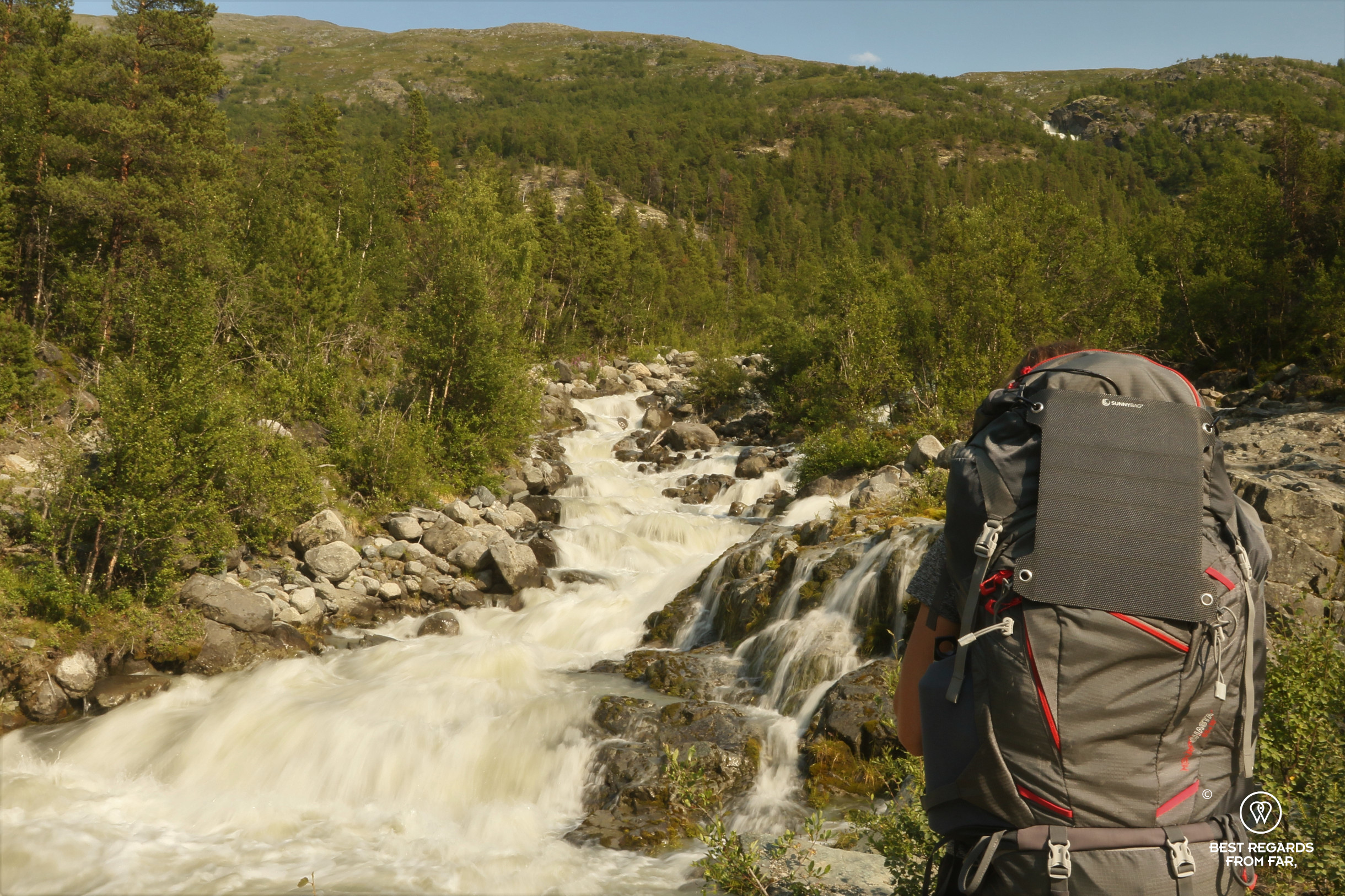 Woman with large backpack looking at the white waters of a river in a pine forest