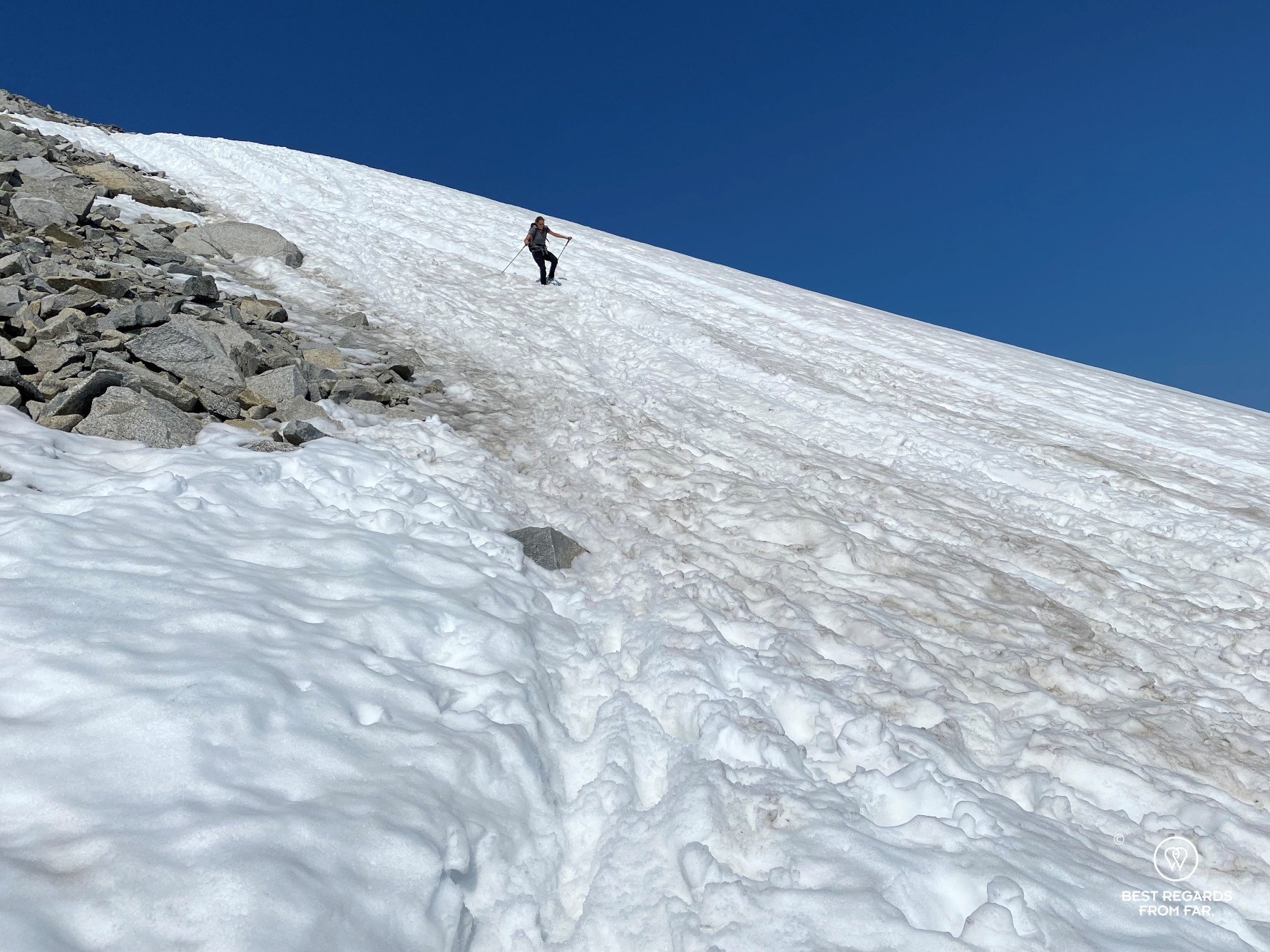 Photographer Marcella van Alphen walking through the snow in summer with blue skies