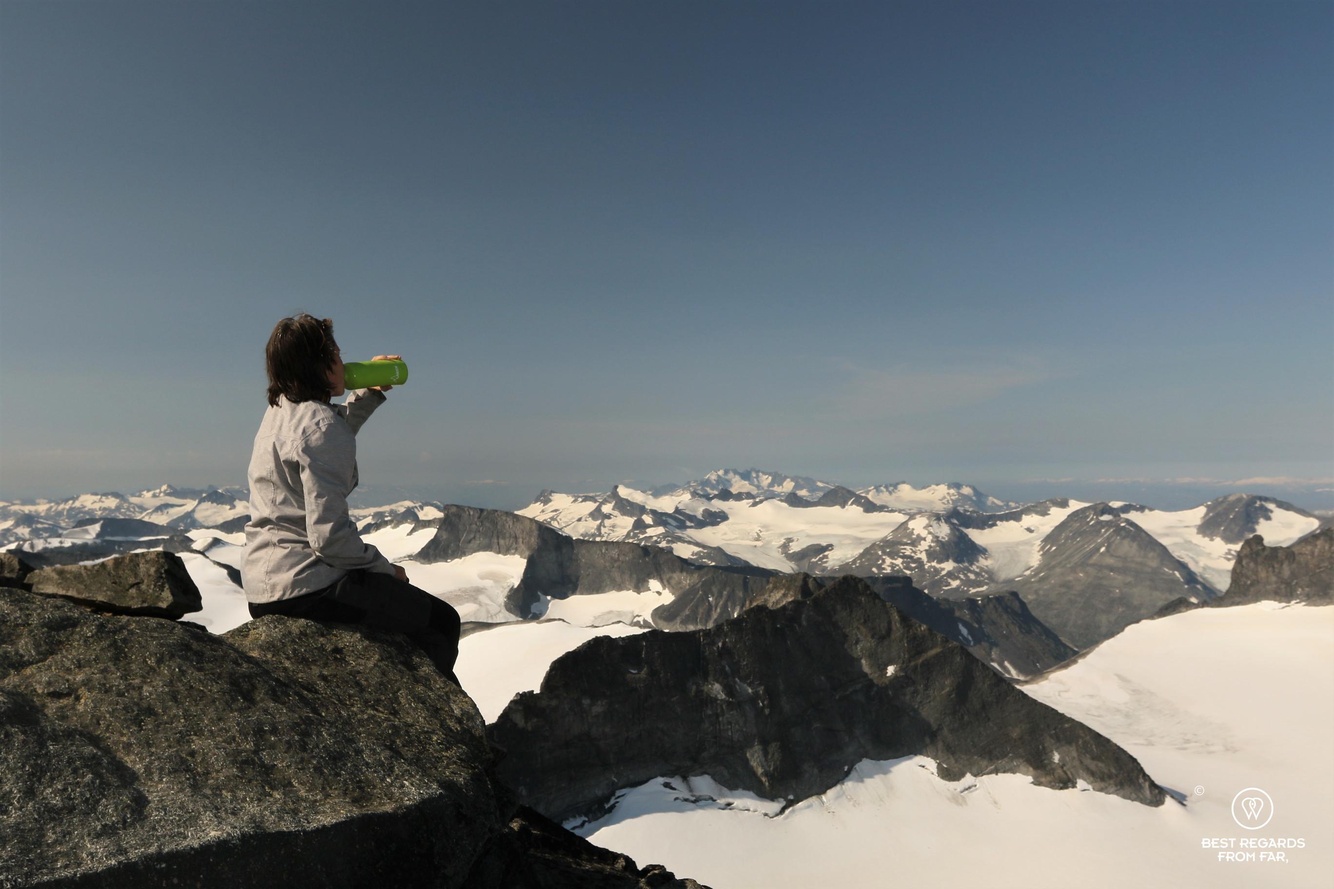 Woman drinking from a green Laken bottle overlooking snowy peaks of Norway in summer