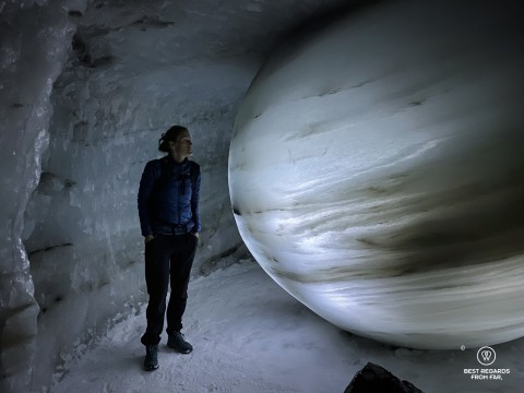 Woman looking at a globe carved out of ice in the ice tunnel, Norway